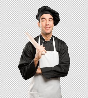 Młody kucharz przy użyciu naczynia do gotowania z gestem wątpliwości