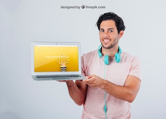 Nowoczesny facet z słuchawkami i laptopem makiety