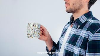 Projekt makiety z młody facet trzyma kubek do kawy