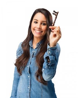 Szczęśliwa dziewczyna pokazując stary klucz