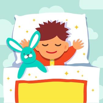 Chłopiec śpiący z jego zabawką królika