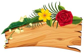 Drewniana tablica z kwiatami i liśćmi na górze