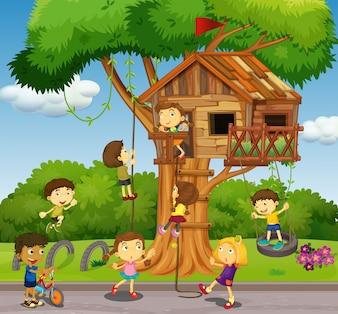Dzieci bawiące się w domku na drzewie w parku