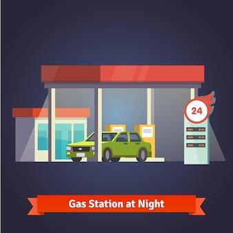 Stacja benzynowa rozżarzonego w nocy. Sklep, tablica cenowa