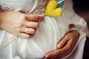 Ładne i delikatne ciąży brzuch i żółte serce na patyku