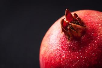 Świeży owoc granatu z kroplami wody na ciemnym tle