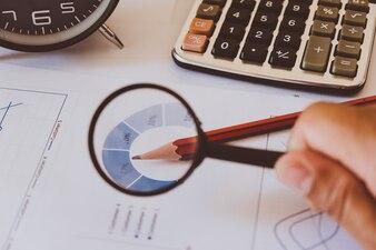Analityka biznesowa i statystyki. Sprawozdanie z działalności biznesmen za pomocą lupy.