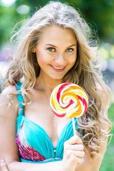 Atrakcyjne blond dziewczyna z lizak w parku latem