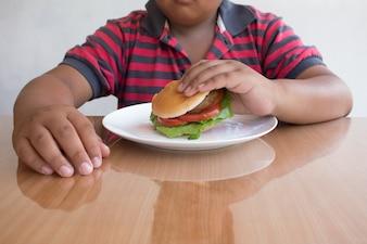 Azjatycki Chłopiec jedzą hamburgera, śmieci żywności niezdrowe dla dzieci