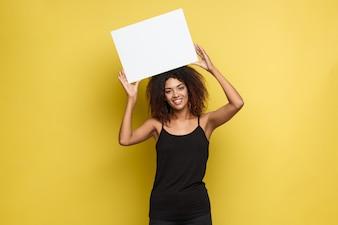 Biznes koncepcji - Zamknij w górę Portret młodych piękne atrakcyjne Afroamerykanów uśmiecha się wykazujące zwykły biały znak pustego. Tło żółte tło pastelowe. Skopiuj miejsce.