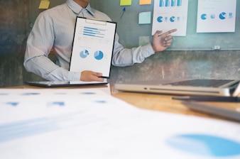 Biznesmen analizowania wykresów inwestycyjnych i naciskanie przycisków kalkulatora nad dokumentami. Koncepcja rachunkowości