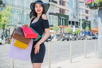 Brunetka dziewczyna stoi na bruk torby gospodarstwa