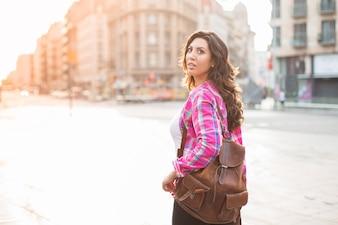 Całkiem młody turysta patrząc wokoło podczas spaceru w dziwnym mieście. Ciekawa kobieta z torebki ze skóry spojrzenie z zainteresowaniem w budynkach wokół. Koncepcja nieznajomego