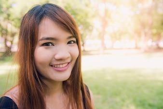 Calm piękna uśmiechnięta młoda kobieta z ponytail korzystających z świeżego powietrza na świeżym powietrzu, relaksujące z zamkniętymi oczami, czując się żywy, oddychając, marzy. Skopiuj miejsce, zielone tło charakter parku. Portret z boku