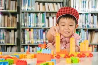 Chłopiec gra z bloków z tworzywa sztucznego w pokoju biblioteki pokoju