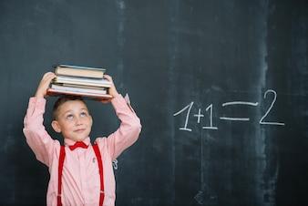 Chłopiec z książkami w klasie matematyki