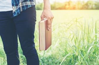 Close-up z ręką trzyma książkę w plenerze