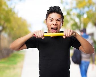 Człowiek o ugryźć gigantyczny ołówek