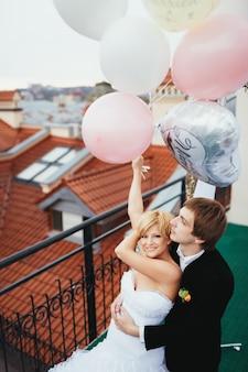 Człowiek obejmując swoją dziewczynę, a ona trzyma balony