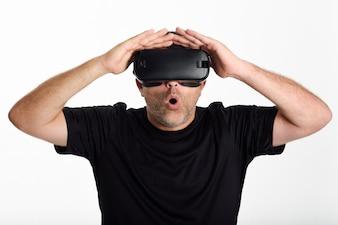 Człowiek patrząc w okulary VR i gestykulując rękami.