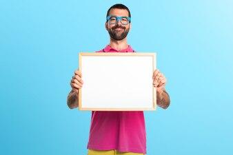 Człowiek z kolorowymi ubraniami gospodarstwa pusty tabliczka na kolorowe tło