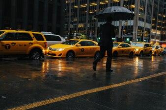 Człowiek z parasolem z taksówek tle