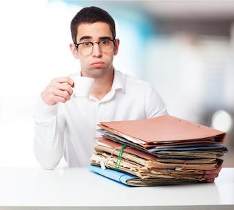 Człowiek ze smutną twarz z folderami i filiżanką kawy