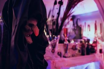 Czarownica stoi przed barem z napojami