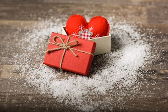 Czerwone serce w szkatułce na desce ze śniegiem