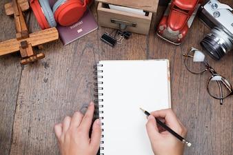 Dłoń trzymająca ołówek i biały notebook blnak na drewnianym stole. Koncepcja przygotowania podróży.