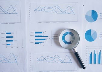 Dane księgowe, wykresy i lupy. Wiele wykresów i wykresów. Refleksja światła i rozbłysku.