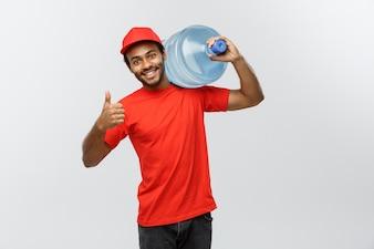 Dostawa koncepcji - przystojny African American dostawy człowiek trzyma zbiornik na wodę. Pojedynczo na tle Szarym Studio. Skopiuj miejsce.
