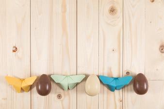 Drewniane tło z motyli papieru i czekoladowych jajek
