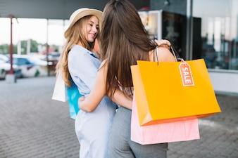 Dwie przytulanie kobiet je na zakupy