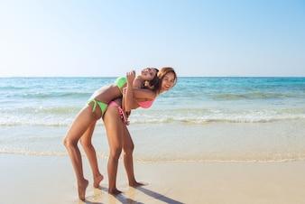 Dwóch młodych azjatyckich brunette najlepszych przyjaciół patrząc na aparat i wysyłanie Ci pocałunek powietrza, mieć sexy ciało slim, noszenie okularów przeciwsłonecznych bikini i biżuteria mody, stwarzających z przodu tropikalnej plaży.
