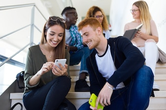 Dwóch studentów korzystających z telefonu komórkowego w uniwersytecie.