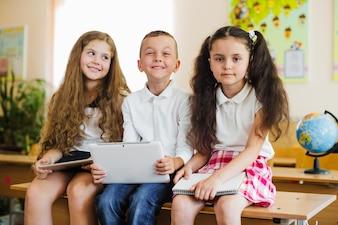 Dzieci siedzi przy biurku w klasie