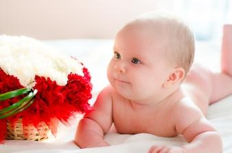 Dziecko leży w pobliżu kwiatów