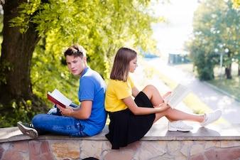 Dziewczyna i chłopiec czytania w parku