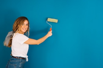 Dziewczyna malowanie niebieskiej ściany