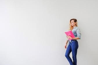 Dziewczyna stwarzających z różowego notebooka