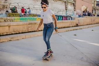 Dziewczynka brunetka jazdy na deskorolce na ulicy