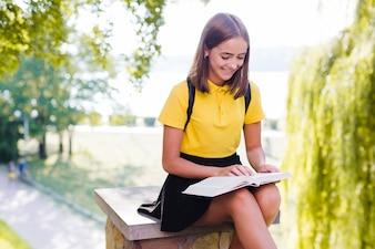 Dziewczynka czyta książkę w parku