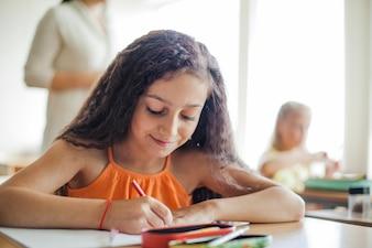 Dziewczynka siedzi na biurko ołówkiem gospodarstwa