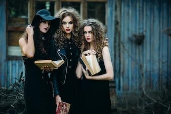 Dziewczyny w przebraniu czarownic posiadających stare książki w rękach