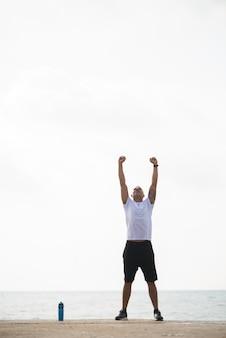 Energiczny człowiek robi rano ćwiczenia na plaży