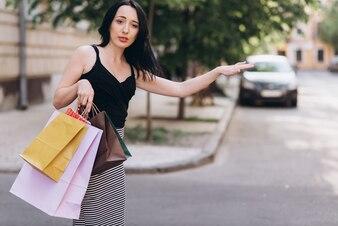 Fashionably ubrana kobieta z kolorowymi torby na zakupy złapać taksówkę na ulicy, koncepcja zakupów