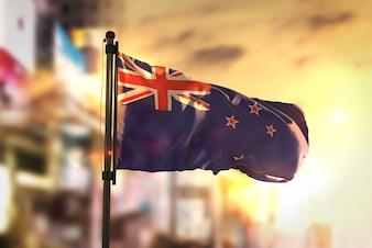 Flaga Nowej Zelandii Przeciw Miastu Zamazany Tła W Sunrise Backlight