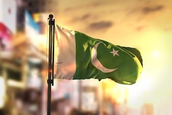 Flaga Pakistanu przeciwko Miastu Zamazane Tło W Sunrise Backlight