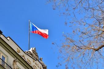 Flaga Republiki Czeskiej w budynku z błękitne niebo i słońca w tle.